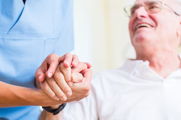 nurse holding hands with a senior man